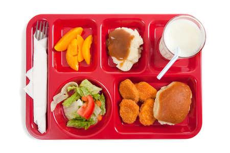 Una bandeja de almuerzo escolar sobre un fondo blanco con copia espacio
