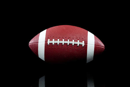 football object: An American football on black background with copy space