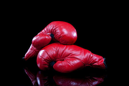 boxing glove: A pair of red leather boxing gloves on a black background with copy space
