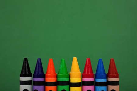 Assorted crayon tops met een groene krijtbord achtergrond Stockfoto