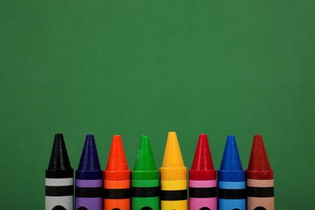Assorted crayon tops with a green chalkboard background