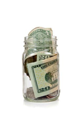 jarra: Dinero en una jarra de vidrio sobre un fondo blanco - ahorro de dinero o sugerencias