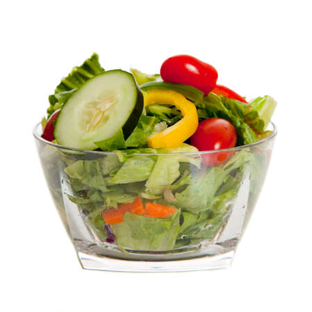 A tossed salad with various vegetables on a white background
