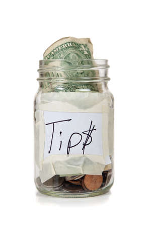 saving tips: a tip jar with coins and bills