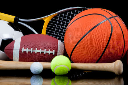 A group of sports equipment on black background including tennis, basketball, baseball, american fotball and soccer and boxing equipment on a black background with copy space photo