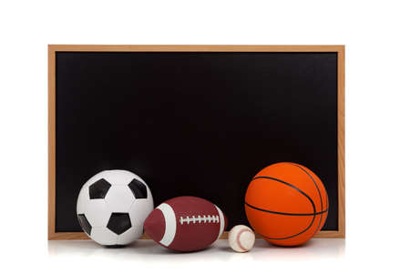 Assorted sports balls including american football, soccer ball, baseball and basketball with a chalkboard background photo