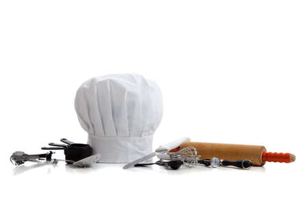 several baking utensils with a chefs hat on white background photo