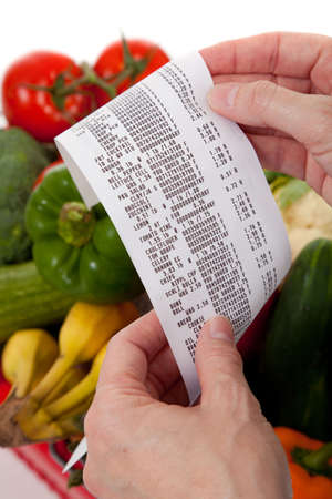 A grecery receipt over a bag of vegetables photo
