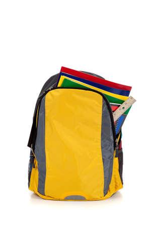 school backpack: Mochila amarilla con escuela de suministros en un fondo blanco Foto de archivo