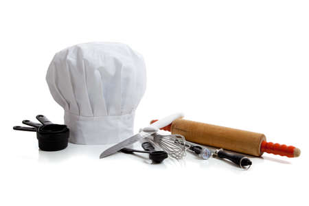 several baking utensils with a chefs hat on white background