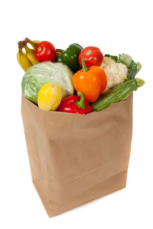 A grocery sack full of vegetables on a white background