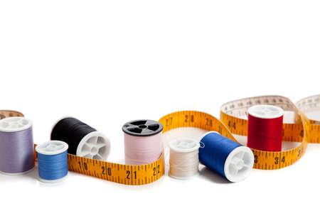 Multi colored thread with a tape measure on a white background with copy space