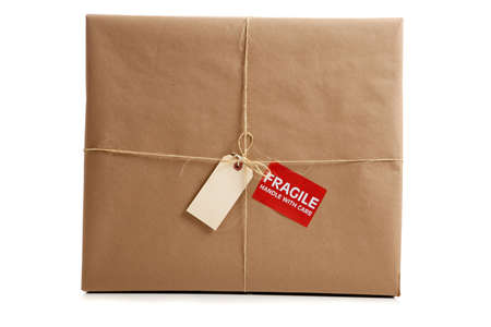 pack string: a Box wrapped in brown craft paper with a blank tag on a white background Stock Photo