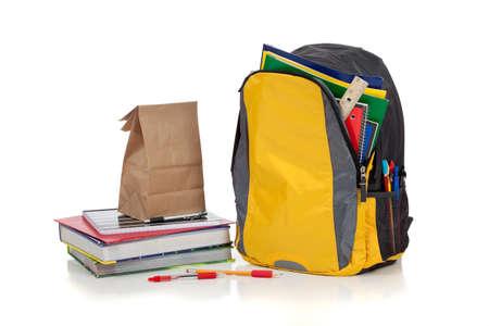 utiles escolares: Mochila amarilla con escuela suministra sobre un fondo blanco