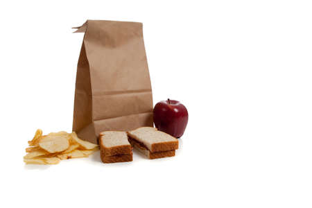 A sack lunch with peanut butter sandwich and a apple photo