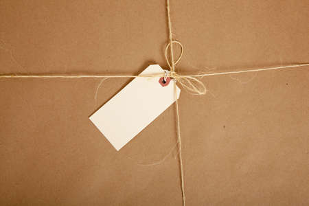 gift wrap: a Box wrapped in brown craft paper with a blank tag on a white background Stock Photo