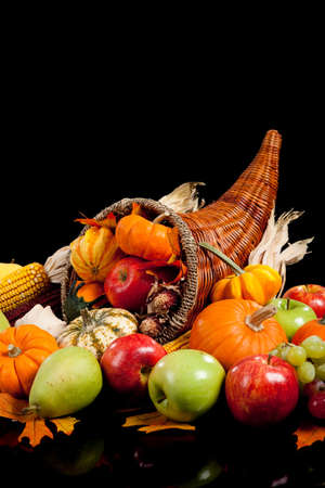 fall arrangement of fruits and vegetables in a cornucopia on a black background photo