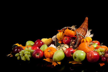 fall arrangement of fruits and vegetables in a cornucopia on a black background