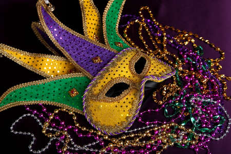 new orleans: glittery gold, green and purple mardi gra mask with beads on a purple background