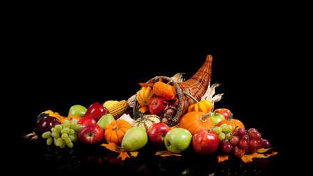 cuerno de la abundancia: disposición de la caída de frutas y verduras en una cornucopia sobre un fondo negro