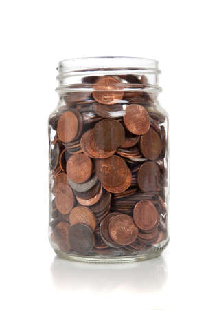 a glass jar full of coins Stockfoto
