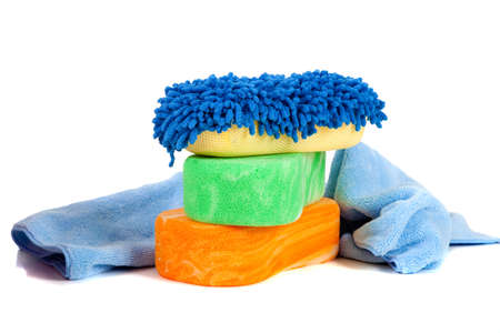 wash: Orange, green and blue sponges with a chami cloth on a white background