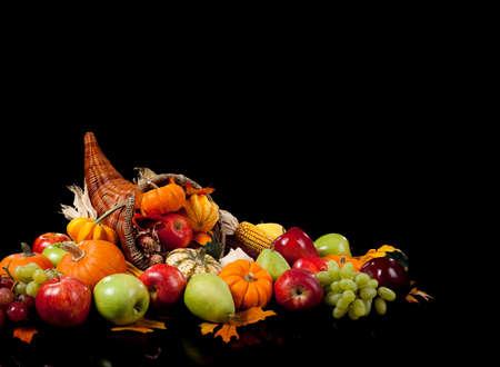 cuerno de la abundancia: disposici�n de la ca�da de frutas y verduras en una cornucopia sobre un fondo negro