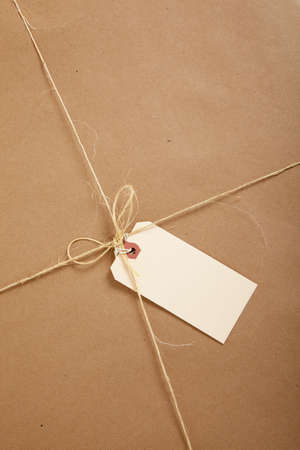 craft paper: a Box wrapped in brown craft paper with a blank tag on a white background Stock Photo