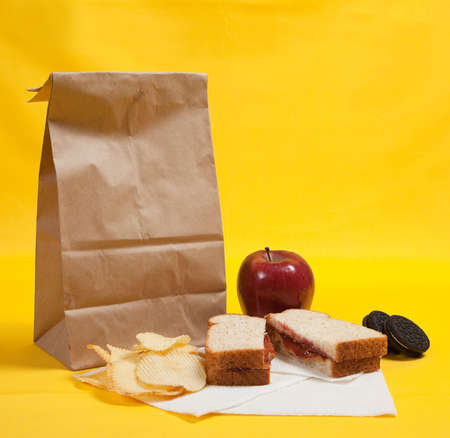 A sack lunch with peanut butter sandwich with apple, chips and cookies photo