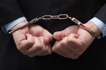 A man in a blue business suit holding hands in handcuffs in front of his chest
