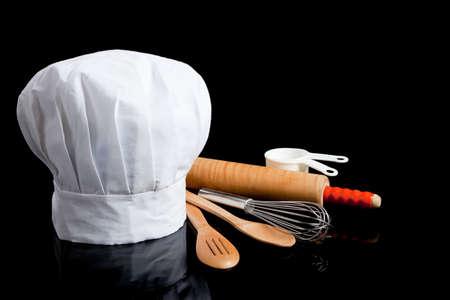 Une toque blanche avec des ustensiles de cuisine, y compris le rouleau à pâtisserie, cuillères de bois, wisk et mesurer les tasses sur un fond noir