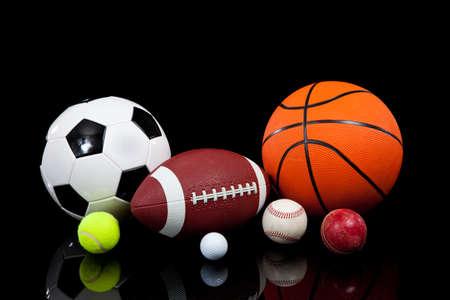 Assorted sports balls including a basketball, american football, soccer ball, tennis ball, baseball, golf ball and cricket ball on a black background Stock Photo - 5766062