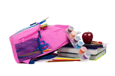 bookbag: Pink and blue backpack with school supplies including paint, pencils, notebooks, pens, markers, erasers and apple on a white background Stock Photo