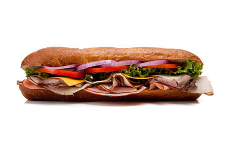 A sub sandwich with lettuce, cheese, tomatoes, red onion, turkey, ham, roast beef and bacon on a white background