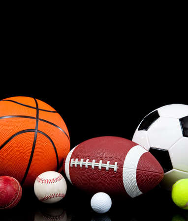Assorted sports balls including a basketball, american football, soccer ball, tennis ball, baseball, golf ball and cricket ball on a black background photo