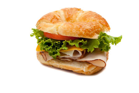 sub: A turkey sandwich on a croissant with lettuce, cheese and tomatoes on a white background
