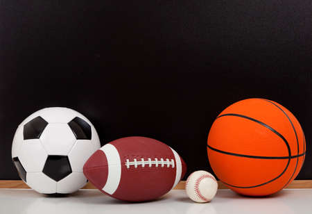 Assorted sports balls including a basketball, american football, soccer ball and baseball on a black chalkboard background Stock Photo - 5766169