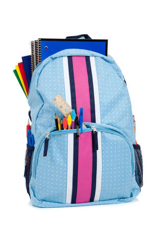 Blue and pink backpack with school supplies on a white background photo