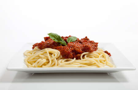 spaghetti sauce: A plate of spaghetti with meat sauce and basil on a white background Stock Photo