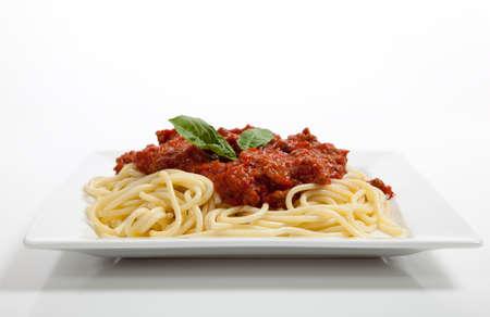 spaghetti saus: Een bord spaghetti met vleessaus en basilicum op een witte achtergrond