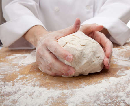 hands kneading bread dough on a cutting board Banco de Imagens