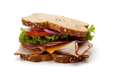 A turkey sandwich on a whole-grain bread with lettuce, cheese and tomatoes on a white background