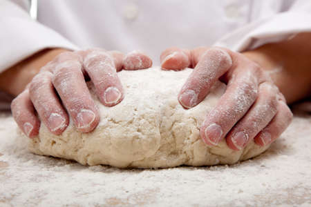 the dough: las manos amasando masa de pan en un tablero de corte