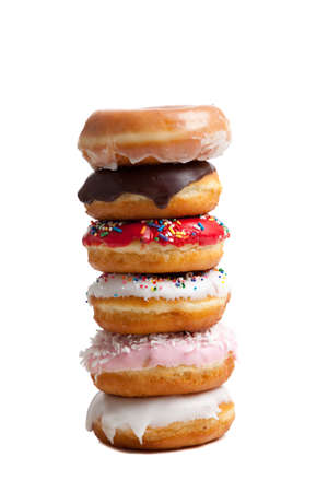 A stack of donuts on  a white background including chocolate icing, sprinkles, coconut and glaze Stok Fotoğraf