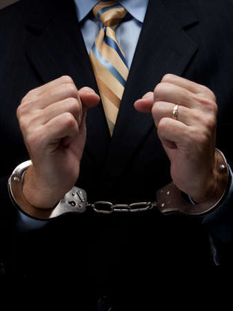 cuffed: A man in a business suit with handcuffs