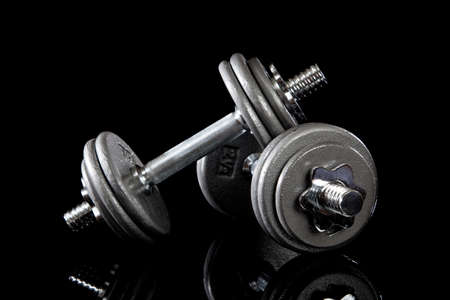 A set of dumbells on a black background