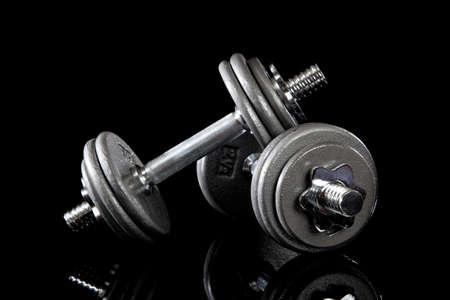 pesas: Un conjunto de dumbells sobre un fondo negro