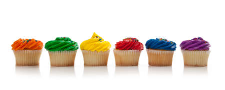blue green background: A red, green, blue, purple, yellow and orange Cupcake with colored sprinkles on a white background Stock Photo