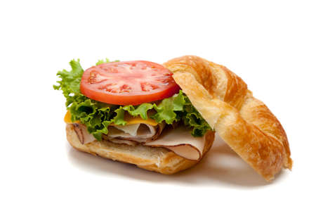 A turkey sandwich on a croissant with lettuce, cheese and tomatoes on a white background