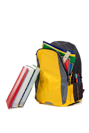 Yellow and black backpack with school supplies inculding composition books, notebooks, folders and text books on a white background photo